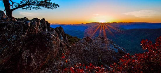 sun rising over shenandoah national park with autumn leaves