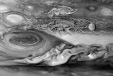 Europa, one of Jupiter's moons, can be seen on the right hand side of this image, drifting past the Great Red Spot