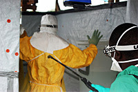 Clinician, assisted by a Médecins Sans Frontières staff member, following a protocol for decontamination before exiting an Ebola Treatment Unit.