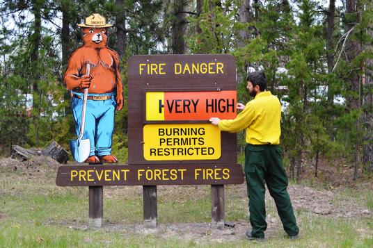 DNR forester adding a High Fire danger sign