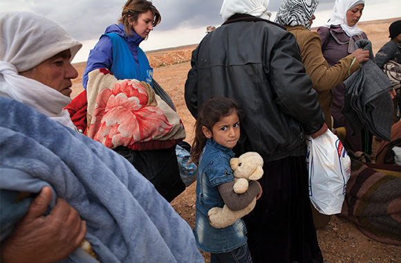 Syrian refugees wait at a transit center in Jordan in 2014.