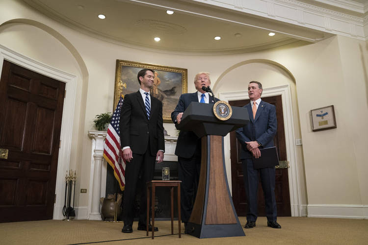 Donald Trump, flanked by Sen. Tom Cotton (R- Ark.) and Sen. David Perdue (R-Ga.), unveils legislation in August that would place new limits on legal immigration. (Jabin Botsford/The Washington Post)