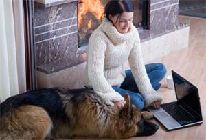 Woman in front of fireplace with dog and laptop