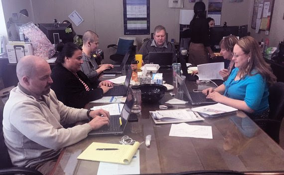 Six WDE staff sit around a conference table and work on their laptops to test the new online platform for Wyoming's statewide assessment.