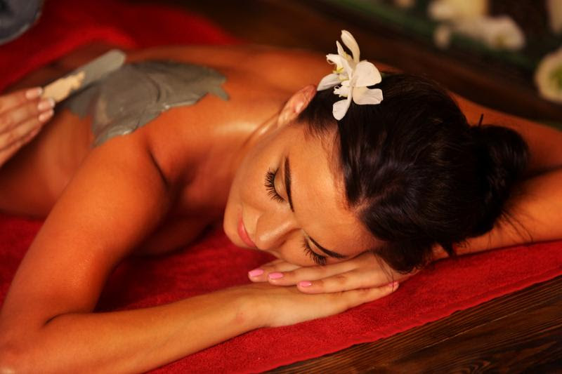 Mud mask of woman in spa salon. Girl on Luxary interior with candles in oriental therapy room. Top view of female with flower lying on wooden spa bed. Rest in an elite beauty salon.