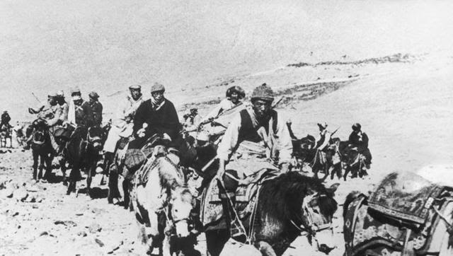 The 14th Dalai Lama fleeing from Tibet to India across the Himalayas, following a failed uprising against the Chinese occupation, in 1959. He is riding a white pony, third from the right (Getty Images)