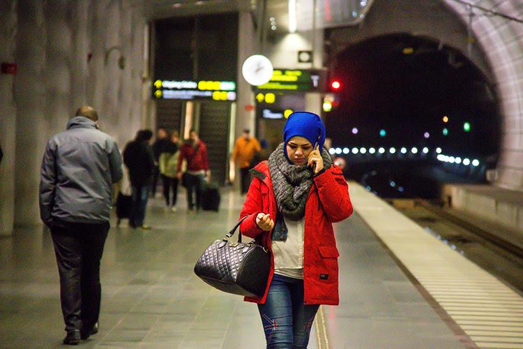 mulher andando e falando ao telefone em uma estação de metrô à noite
