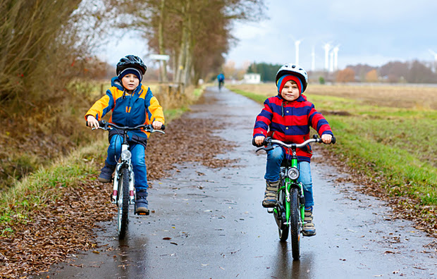 Two young boys riding bicycles on a paved path.