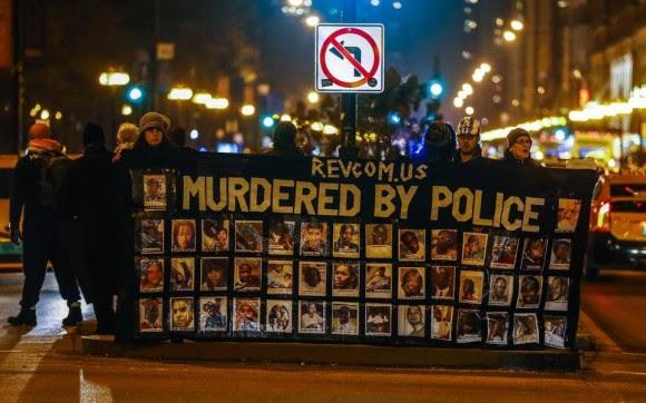 Manifestantes bloquean el paso en Michigan Avenue este martes 24 de noviembre de 2015, en Chicago (EE.UU.), después de que las autoridades judiciales de Chicago (EE.UU.) anunciaron el procesamiento por asesinato de un policía blanco por la muerte de un joven negro al que disparó 16 balazos en un incidente ocurrido hace un año y que fue grabado en vídeo. El agente implicado en el incidente, Jason Van Dyke, de 37 años, se entregó esta mañana a las autoridades y está pendiente de comparecer en un vista judicial para decidir si se le concede la libertad condicional.
