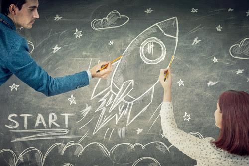 people drawing a rocket on a chalkboard