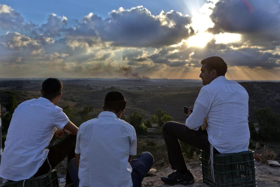 Israelis sat on a hill overlooking the Gaza Strip as smoke rose from the scene of an airstrike.