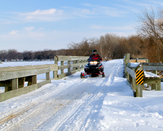 A snowmobiler crosses a snow covered bridge