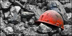 The figure above is a photograph showing a miner's helmet among coal.