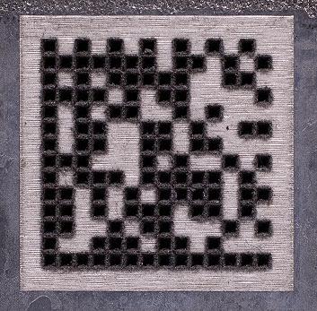 Code matriciel de données gravé au laser avec des cellules noires et blanches.