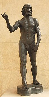 Nude man holding is hand out, as if explaining a point.