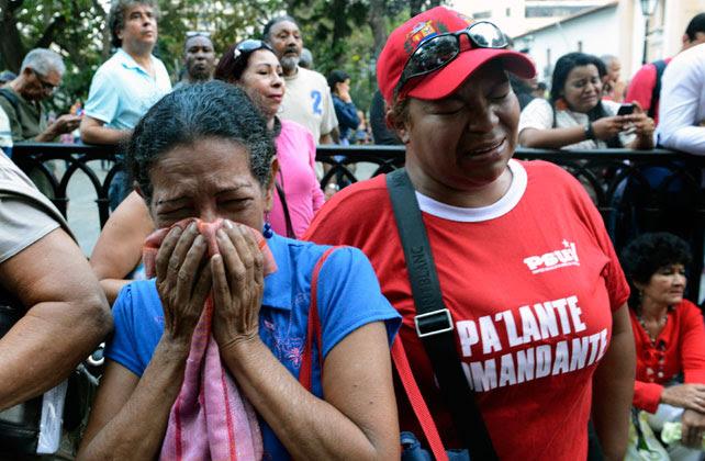 Dos venezolanas lloran en una marcha en homenaje al recuerdo de Hugo Chávez.