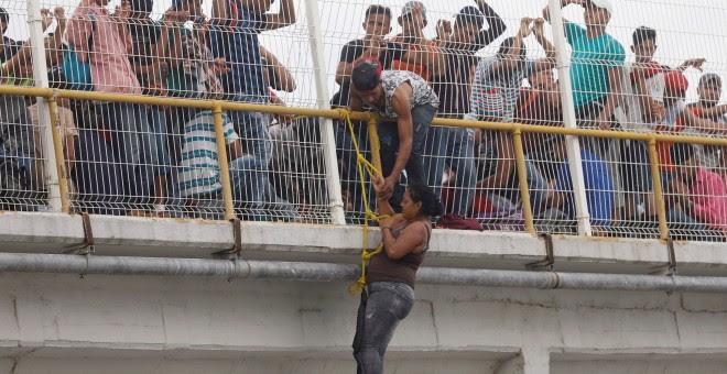 Una migrante trata de escalar el puente que cruza el río que une México con Honduras.REUTERS/Edgard Garrido