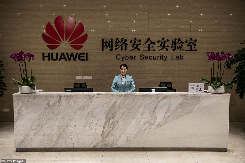 A member of Huawei's reception staff stands at her desk at the Cyber Security Lab at the company's production campus