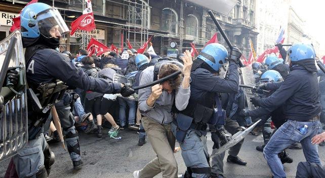Un antidisturbios golpea a una manifestante durante la protesta contra la austeridad en Roma.