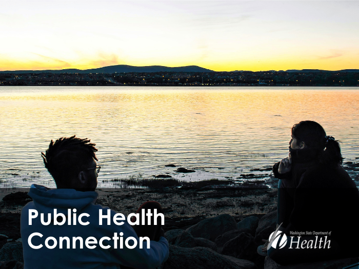 Two friends sit at the waterfront looking quietly into the sunset.