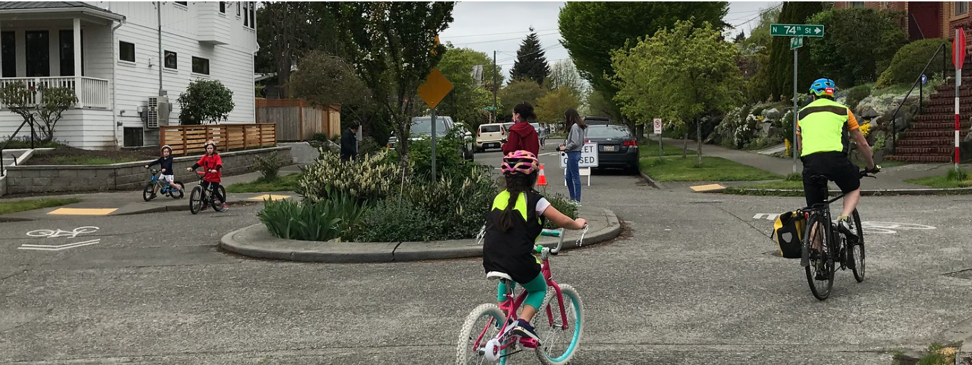 A family bikes around a traffic circle on a local Stay Healthy Street.