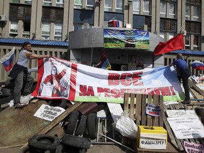 Activistas colocan una pancarta para pedir la convocatoria de un referéndum sobre el estatus de la región delante de la sede del Servicio de Seguridad, ocupada por activistas prorrusos, en Lugansk (Ucrania)