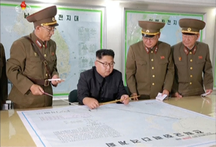 North Korean leader Kim Jong Un reviews the plan for landing missiles near the U.S. territory of Guam. (KRT/Reuters).
