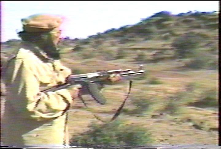 The spiritual leader of Muslims of America is Sheikh Mubarik Gilani, shown here shooting a rifle in a Soldiers of Allah recruiting video.