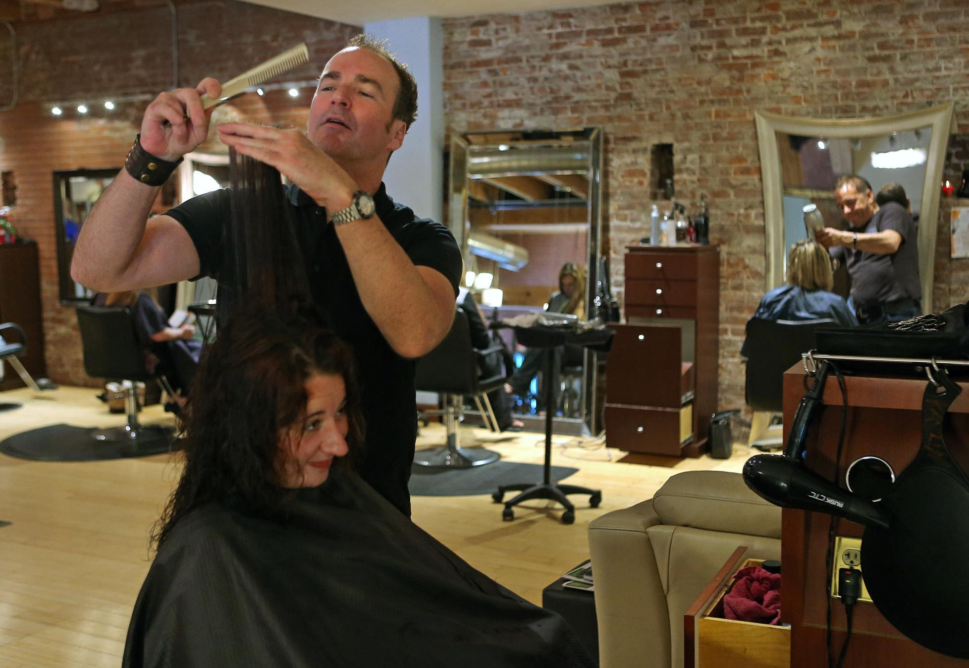 David McCarthy, a STOP program graduate, cut a customer's hair in a Worcester salon.