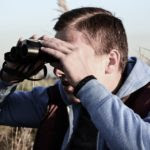 Young Male Spying Binocular Looking Forward Person