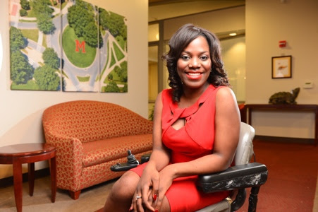 """Ola, a 2015 """"No Boundaries"""" participant, wears a red dress and poses in her wheelchair"""