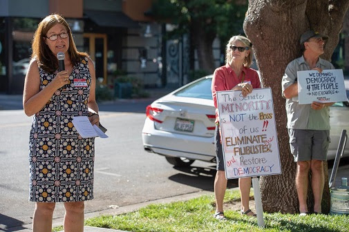 """Kelly Wilkerson, organizer for Sister District CA-03, speaks at the rally. In the background, activists hold signs reading """"The Senate minority is not the boss of us!! Eliminate the filibuster and restore democracy"""" and """"We demand democracy 4 the people- no excuses"""""""
