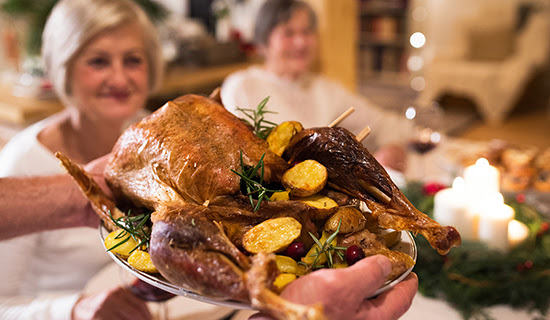 Close up of a roasted turkey being brought to the dinner table on a serving tray.