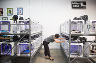 Carly Nakayama checks on the 3-D printing process in the San Diego office of the tech cobbler company Feetz.