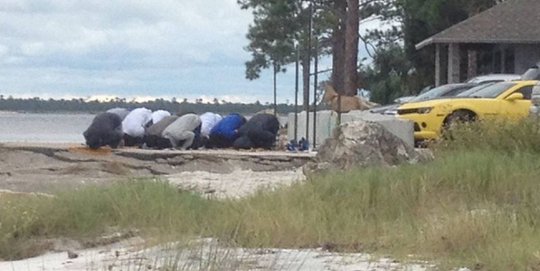 A group of Muslim men praying on a Florida beach has set some officials on edge. (Credit: Facebook)