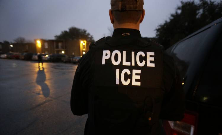 Immigration and Customs Enforcement agents enter an apartment complex looking for a specific undocumented immigrant convicted of a felony during a 2015 operation in Dallas. (LM Otero/AP)