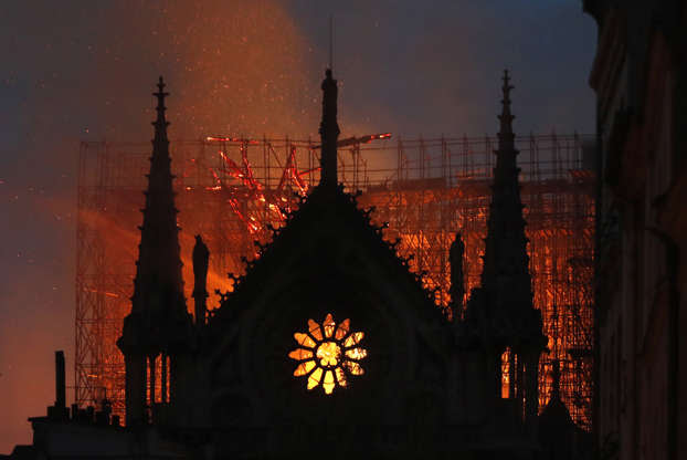 Slide 8 of 31: Flames and smoke rise from Notre Dame cathedral as it burns in Paris, Monday, April 15, 2019. Massive plumes of yellow brown smoke is filling the air above Notre Dame Cathedral and ash is falling on tourists and others around the island that marks the center of Paris. (AP Photo/Thibault Camus)