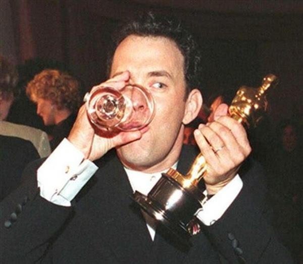 Tom Hanks bebendo com o Oscar na festa da premiação