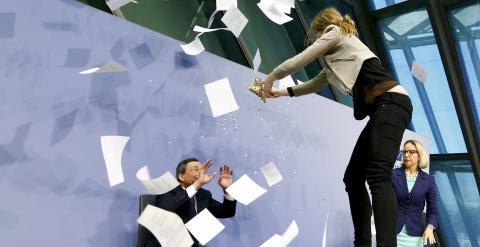 Una activista salta sobre la mesa desde la que el presidente del BCE, Mario Draghi, ofrece su rueda de prensa mensual en la sede de la entidad monetaria de la Eurozona. REUTERS/Ralph Orlowski