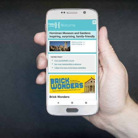 A mobile phone showing the Horniman website