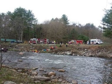wide angle of a creek with various rescue crews pulling a man and his car out of the creek