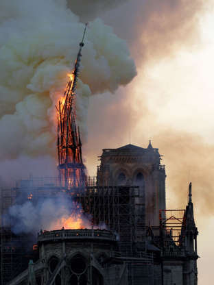 Slide 13 of 31: The steeple of the landmark Notre-Dame Cathedral collapses as the cathedral is engulfed in flames in central Paris on April 15, 2019. - A huge fire swept through the roof of the famed Notre-Dame Cathedral in central Paris on April 15, 2019, sending flames and huge clouds of grey smoke billowing into the sky. The flames and smoke plumed from the spire and roof of the gothic cathedral, visited by millions of people a year. A spokesman for the cathedral told AFP that the wooden structure supporting the roof was being gutted by the blaze. (Photo by Geoffroy VAN DER HASSELT / AFP)        (Photo credit should read GEOFFROY VAN DER HASSELT/AFP/Getty Images)
