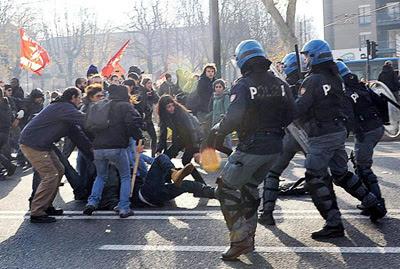 Manifestantes y antidisturbios se enfrentan durante una protesta convocada con motivo de la huelga general en Turín.